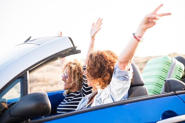 コンバーチブル車と座席の後ろの荷物に乗った大人の白人女性のカップル