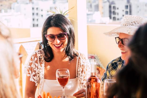 レストランで屋外ランチタイムを一緒に楽しんでいる大人の陽気な幸せな女性のカップル