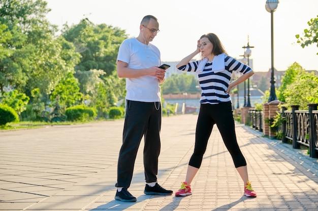 スポーツの練習の後に話し、公園でジョギングして休んでいる大人のカップル。中年のアクティブな健康的なライフスタイル、スポーツ、フィットネス