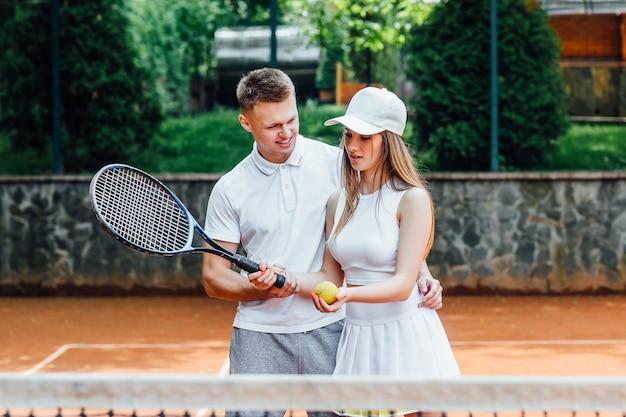 성인 테니스 선수의 커플입니다. 운동 여자와 남자는 쾌활한 미소를 지으며 라켓을 들고 유니폼을 입고 있습니다.