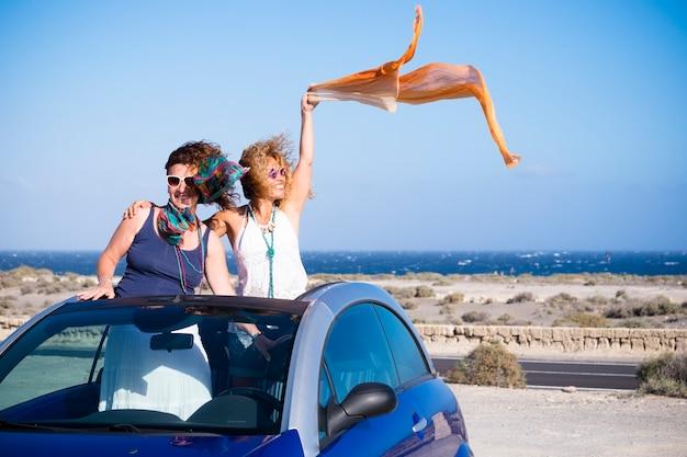 大人の女性の友人のカップルがコンバーチブル車の中で立ち、車で夏休みの旅行休暇を楽しむ