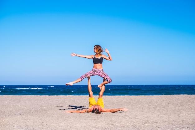 砂浜で一緒に運動をしている大人のカップル-海を背景にヨガまたはアクロヨガをしている2人-彼のガールフレンドを足で抱きしめている男