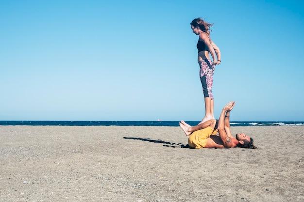 Пара взрослых, занимающихся йогой или акройогой в тишине на пляже - женщина и мужчина сосредоточены на совместной работе - город на заднем плане