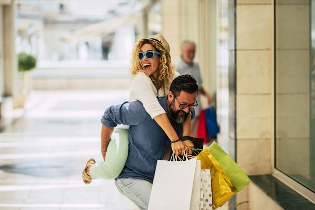 Пара взрослых влюбляются вместе и делают покупки в торговом центре, развлекаясь - мужчина держит жену за спину и несет ее
