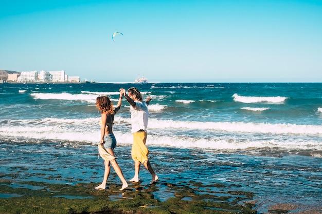 발에는 물이 있고 배경에는 바다가 있는 바위 위의 해변에서 행복한 산책을 하는 성인 부부 - 팔 벌리고 자유 개념