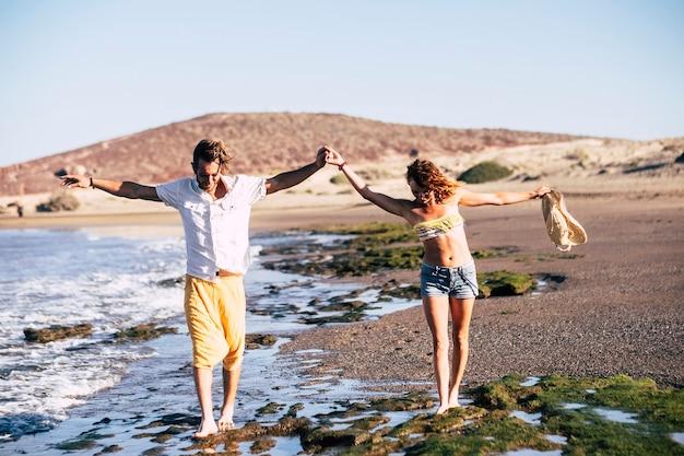 腕を上げてビーチで一緒に歩いている大人のカップル-一緒に旅行している関係の2人
