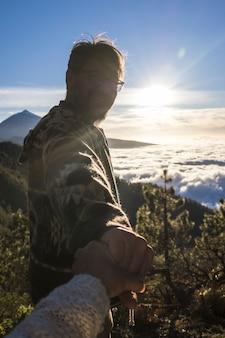 冒険旅行者のカップル。男性のシルエットは、山の風景をハイキングする手をつないでいる女性をフォローしています。山頂でのハイキングを楽しむカップル
