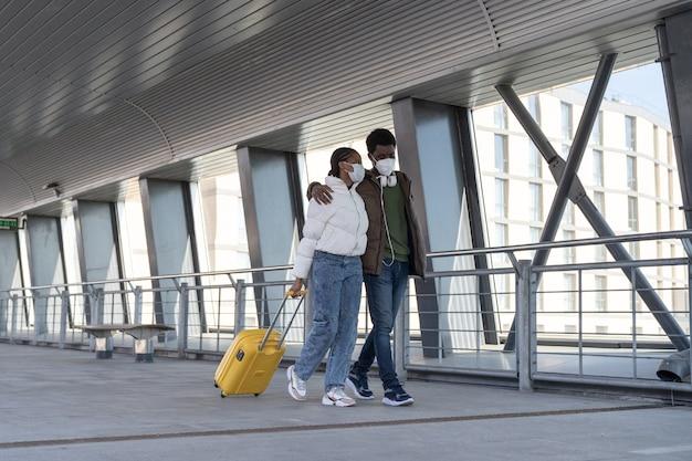 防護マスクを着たアフリカ人観光客のカップルが、出発のために空港ターミナルでスーツケースを持って歩く