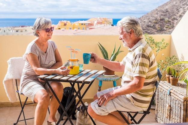 老紳士と女性のカップルは、日光の下で2匹の面白いパグ犬と一緒に屋上テラスでフルーツジュースを飲みます。素晴らしい引退したコンセプトのための素晴らしいオーシャンビュー