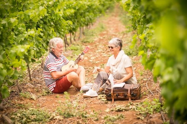 別の成熟した旅行者のカップルがブドウ園に座って滞在します