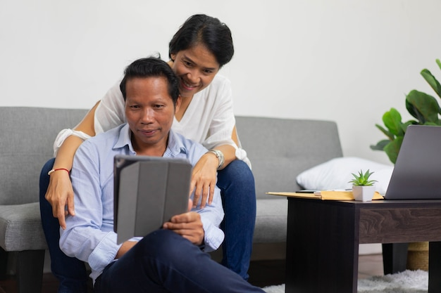 ビデオ通話会議にデジタルタブレットを使用しながらリビングルームに座っているアジアの親のカップル