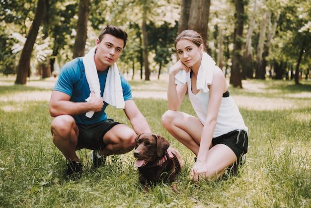 緑豊かな公園で犬と一緒に運動選手のカップル