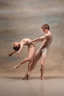 Пара танцоров балета позирует на сером пространстве