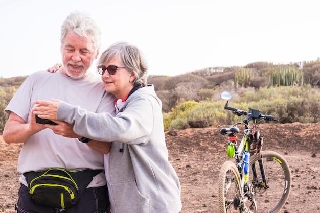 美しい白人のアクティブな大人のシニアのカップルは、マウンテンバイクを楽しんでいます。一緒にgpsマップをチェックして家に帰る屋外スポーツバイク活動の老いも若きライダー