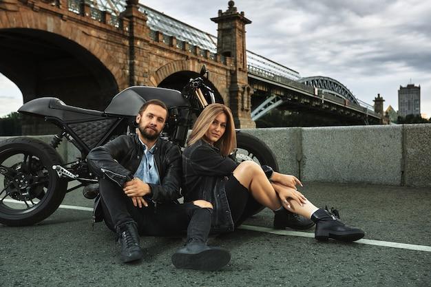 美しい恋人たちのカップルが街の道路でバイクの横に抱き締めて座っています