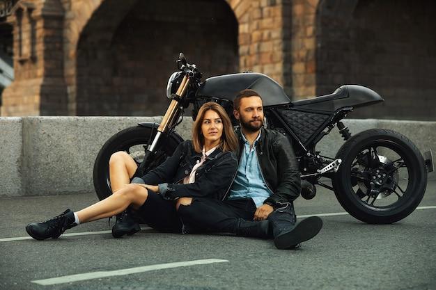 Пара красивых влюбленных сидят обниматься рядом с мотоциклом на дороге в городе