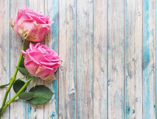 青い木製の背景に美しいピンクのバラのカップル