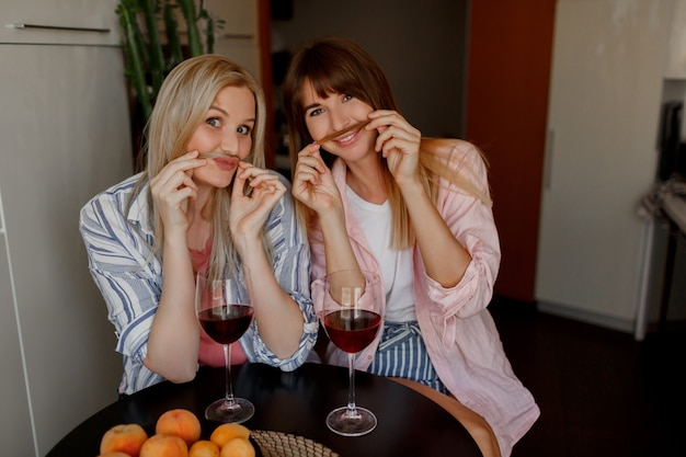 Пара красивых женщин пьет вино дома. гримасничаю. в пижаме.