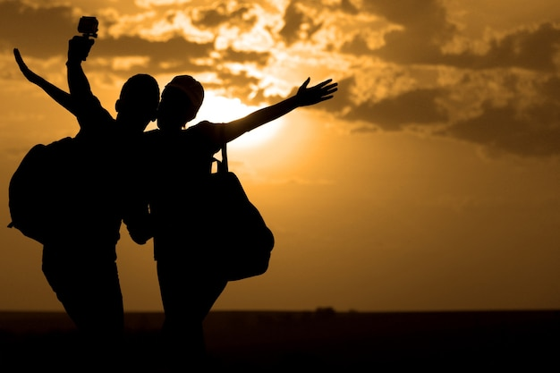 日没時に自分撮りをしている親友のカップル