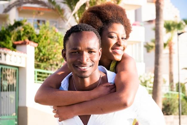 黒人の若い男性と女性のカップルは、友達の活動を運ぶピギーバックで一緒に楽しんで笑顔になります-幸せな人々の概念は、屋外での友情と関係を楽しんでいます