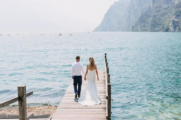 湖で木製のピアスの上を歩く新郎新婦のカップル。