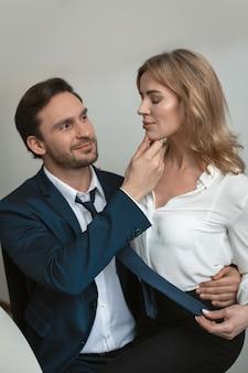 Пара деловых мужчин и женщин, одетых в формальную одежду, флиртует, обнимая и касаясь друг друга