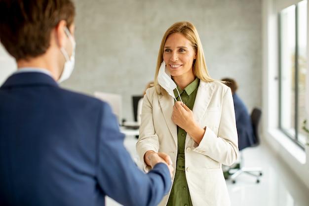 コロナウイルスの流行のためにオフィスで握手し、保護フェイスマスクを着用しているビジネスマンのカップル
