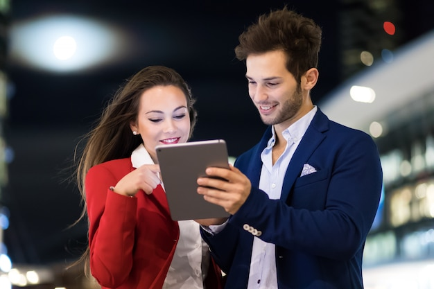 현대 도시 속에서 밤에 야외 태블릿을 사용하는 사업 사람들의 커플