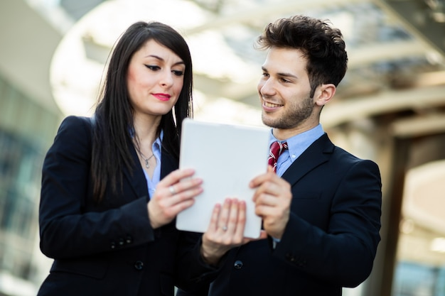 屋外でタブレットを使用しているビジネスマンのカップル