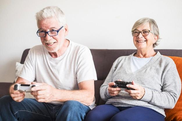 소파에 앉아 집에서 함께 비디오 게임을 하는 백인 은퇴한 노인 부부 - 성숙한 여성과 결혼한 남성 - 두 사람은 영원히 약혼 - 컨트롤러 또는 조이스틱을 들고