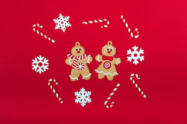 赤い背景の上のクリスマスジンジャーブレッドマンのカップル。新年とギフトのコンセプト