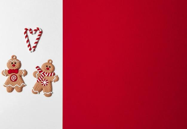 赤い空きスペースと白い背景の上の愛の心の形でキャンディーとクリスマスジンジャーブレッドマンのカップル
