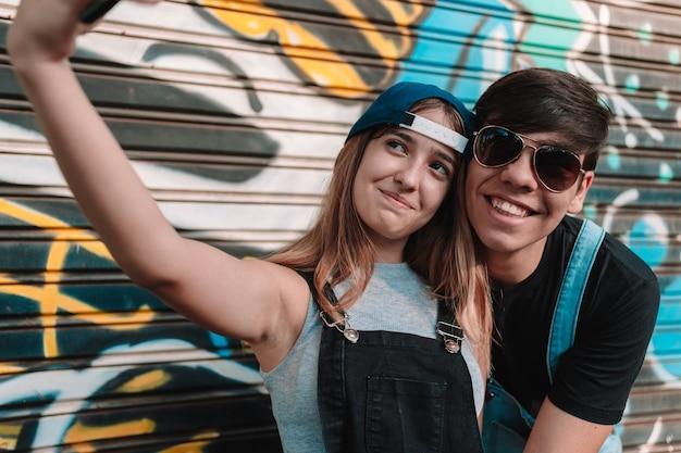 自撮りをしているクールな十代の若者たちのカップル