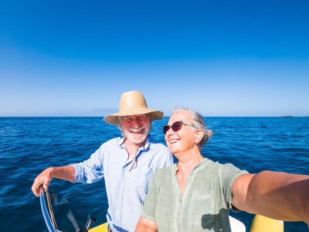 바다 한가운데에서 함께 즐기고 즐기는 귀여운 성숙한 사람 또는 노인 커플