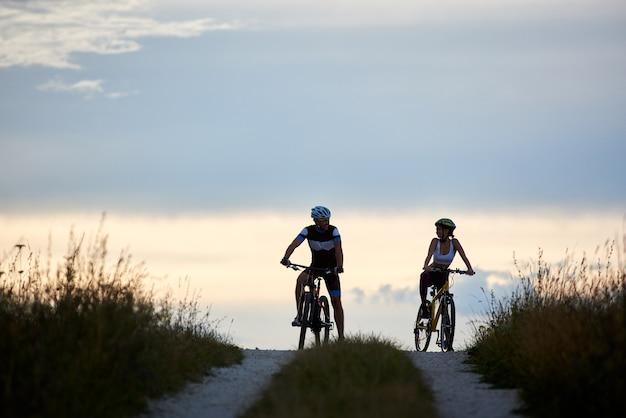 田舎道で自転車に座っているサイクリストのカップル