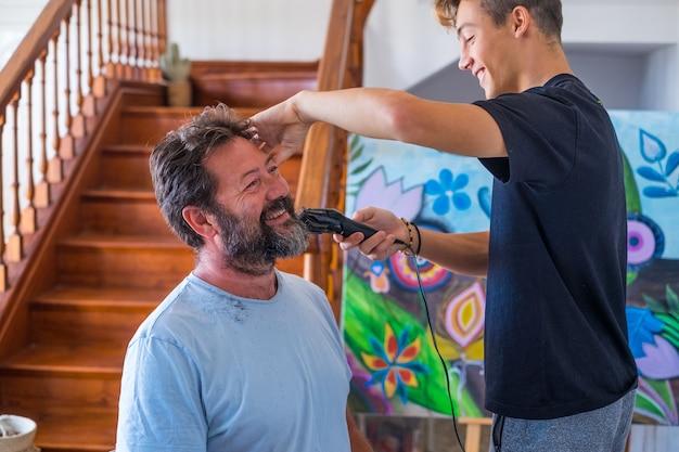 Пара папы и сына дома смеются и веселятся вместе, стригут бороду отца на карантине - улыбаются и играют в парикмахерскую или самодельную парикмахерскую