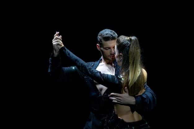 Пара танцоров, выступающих на изолированном черном фоне. мускулистый красивый мужчина и привлекательная женщина