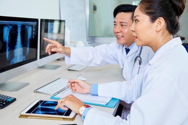 Пара врачей обсуждают рентгеновское изображение