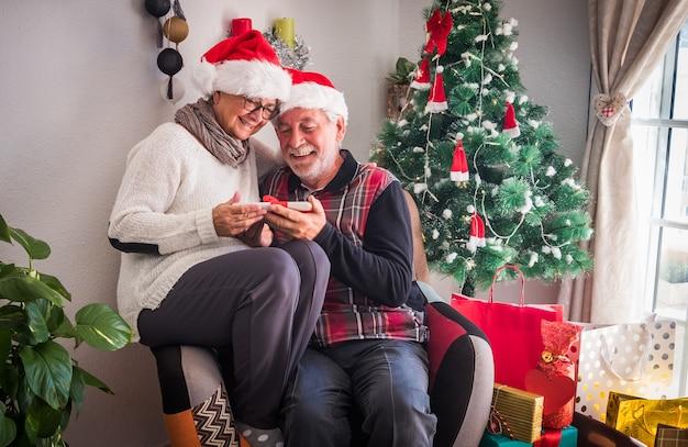 산타 모자를 쓰고 같은 안락의자에 함께 앉아 있는 노인 몇 명. 크리스마스 선물로 받은 태블릿을 들고. 백그라운드에서 선물과 크리스마스 트리