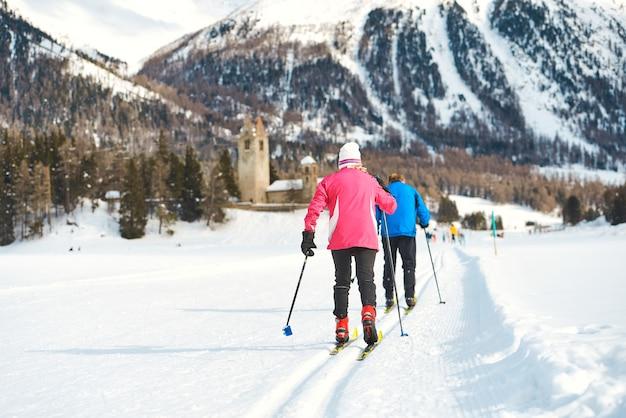 노인 부부는 크로스 컨트리 스키를 연습합니다.