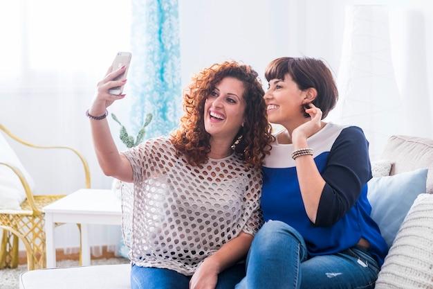 Пара кавказских молодых друзей женщин, делающих селфи на современный телефон, чтобы поделиться в социальных сетях