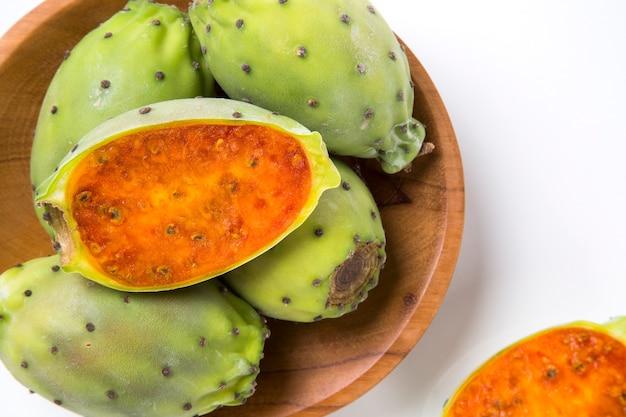 木製の表面上の木製の鍋にインドのイチジクのカップル。新鮮な果物。