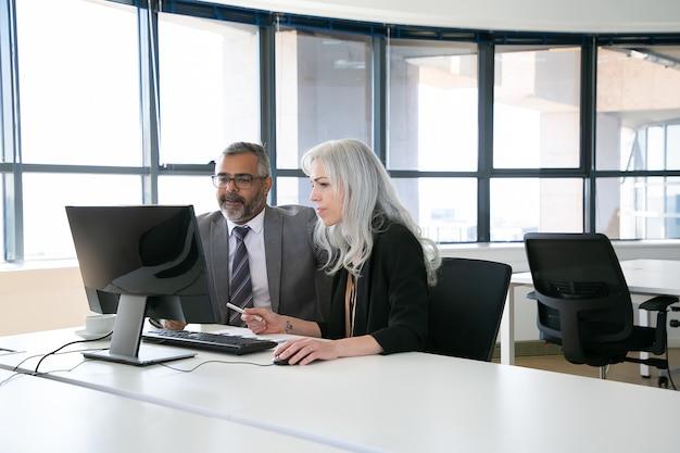 Пара сосредоточенных коллег по бизнесу, просматривающих контент на мониторе компьютера, держа перо и мышь. концепция делового общения и совместной работы