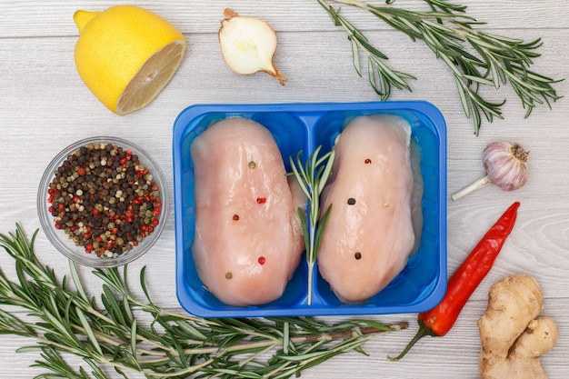Пара свежих сырых куриных грудок или филе в пластиковом контейнере с корнем имбиря, перцем чили, чесноком, луком, лимоном, душистым перцем в стеклянной миске и розмарином на деревянном фоне. вид сверху.