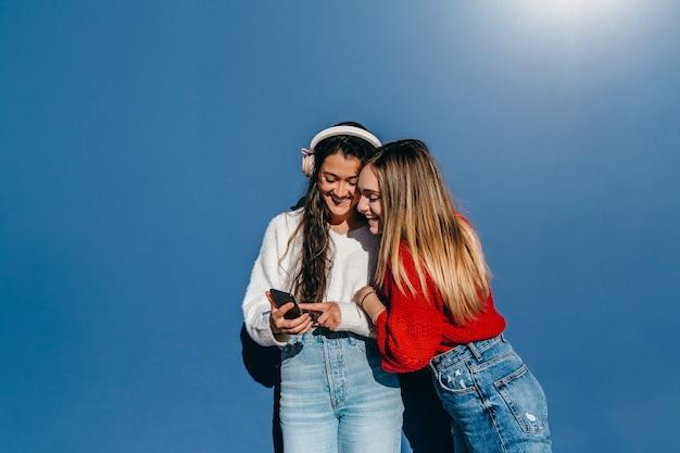 画面を見ながらヘッドフォンで携帯電話の音楽を聴いている友人のカップル、1人の金髪と1人のブルネット