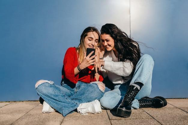 青い壁の前の床に座っている彼らの携帯電話を見て笑っている長い髪の友人のカップル、1人のブロンドと1人のブルネット。