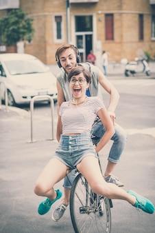 Пара друзей молодой человек и женщина езда на велосипеде