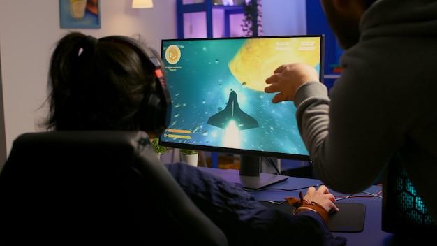 Пара геймеров, играющих в многопользовательскую игру на мощном компьютере дома с профессиональными наушниками