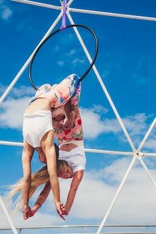 アクロバティックなフィットネス展示会を行っている逆の位置にある女の子のカップルは、健康的な代替スポーツライフスタイルのためにバランスの取れた位置に円を描いて屋外で活動を示しています