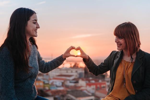 夕日の中で愛を祝いながら手でハートを作る女の子のカップル
